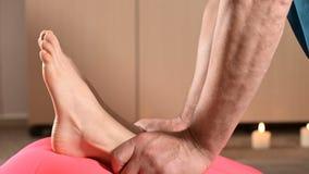 Физиотерапевт конца-вверх a мужской протягивает соединения колена к пациенту маленькой девочки Ручная терапия здоровья акции видеоматериалы