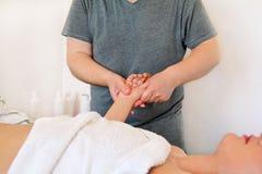 Физиотерапевт массажируя ладонь женщины на здоровье и центе курорта Стоковая Фотография