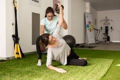 Физиотерапевт помогая молодой кавказской женщине с wi тренировки Стоковое Изображение RF