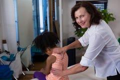 Физиотерапевт портрета давая задний массаж к пациенту девушки Стоковые Изображения RF
