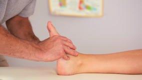 Физиотерапевт работая на ноге пациентов сток-видео