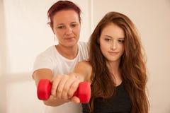Физиотерапия - молодая женщина делая тренировки руки с терапевтом стоковое фото