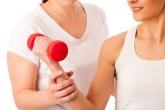 Физиотерапия - терапевт делая excercises руки с гантелями f стоковое изображение rf