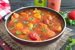 Филе рыб сварило в томатном соусе с зелеными горохами и томатами вишни на плите на деревянной предпосылке Здоровая концепция eatn Стоковые Фотографии RF