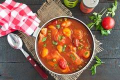 Филе рыб сварило в томатном соусе с зелеными горохами и томатами вишни на плите на деревянной предпосылке Здоровая eaing концепци Стоковое Фото