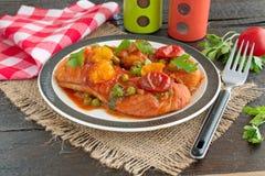 Филе рыб сварило в томатном соусе с зелеными горохами и томатами вишни на плите на деревянной предпосылке Здоровая концепция eatn Стоковые Фото