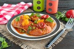 Филе рыб сварило в томатном соусе с зелеными горохами и томатами вишни на плите на деревянной предпосылке Здоровая концепция eatn Стоковая Фотография RF