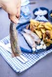 Филе сельдей в женской руке, испеченной в картошках печи и соленьях и луках Очень вкусная традиционная еда Голландии голландско стоковая фотография rf