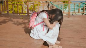 Филиппинская девушка школьницы с рюкзаком сидящ и плачущ около настроения тропического побережья унылого стоковые фото