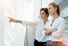 Финансист молодой женщины показывая что-то к ее партнеру через окно офиса пока стоящ в прихожей, Стоковое фото RF