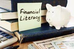 Финансовая грамотность написанная на ручке и копилке как символ сбережений стоковые фото