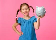 Финансовая концепция денег кармана детей девушка ребенка с копилкой на покрашенной розовой предпосылке стоковая фотография rf