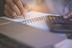 Финансовые данные анализируя сочинительство руки и рассчитывать калькулятор Стоковая Фотография RF