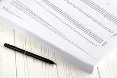 Финансовые бумага и ручка на белом деревянном столе Стоковое фото RF