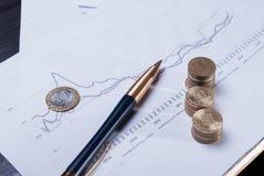 Финансовые диаграммы с лежа ручкой и стогами монеток Стоковая Фотография RF