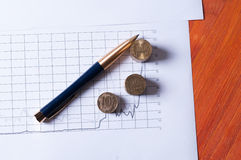 Финансовые диаграммы с лежа ручкой и стогами монеток Стоковое Изображение