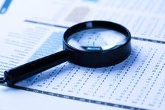 Финансовые документы с лупой стоковые изображения