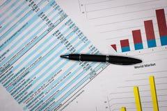Финансовые отчеты рассматривают и анализируют с цветастыми диаграммами и таблицами стоковое фото