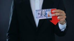 Финансовый консультант держа банкноты доллара показывая большие пальцы руки вниз, падающ видеоматериал