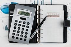 Финансовый дневник и ручка лежа в диаграмме Стоковое Фото
