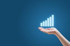 Финансовый план-график в руке на голубой предпосылке Стоковое фото RF