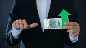 Финансовый эксперт держа банкноты русского рубля показывая большие пальцы руки вниз, рост видеоматериал