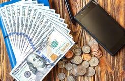 Финансы дела и сохраняют концепцию денег Крупный план долларовых банкнот, монеток, телефона, ручки и тетради американца 100 Стоковые Фото