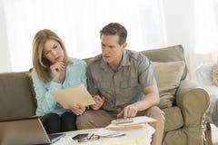 Финансы дома зрелых пар расчетливые на софе Стоковые Изображения