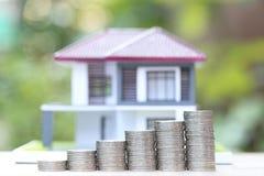 Финансы, стог денег монеток и модельный дом на естественных зеленых предпосылке, капиталовложениях предприятий и недвижимости стоковое фото