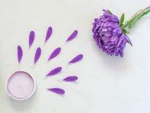 Фиолетовая косметическая сливк и фиолетовые лепестки цветка Стоковая Фотография