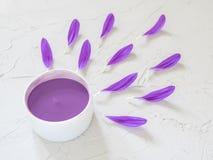 Фиолетовая косметическая сливк и фиолетовые лепестки цветка Стоковые Изображения