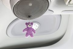 Фиолетовая кукла плюшевого медвежонка висит на дикторах в комнате автомобиля стоковое фото rf