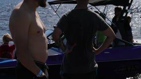 Фиолетовая моторная лодка с молодой женщиной плавает близрасположенная пристань вполне людей на лете сток-видео