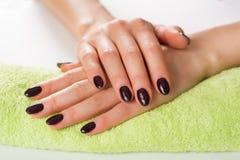 Фиолетовое искусство ногтя с сусал, женскими руками на зеленом полотенце стоковое изображение rf