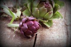 Фиолетовые артишоки на деревенской деревянной предпосылке Стоковое Фото