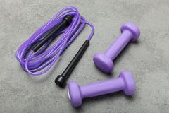 Фиолетовые гантель и веревочка на конкретной предпосылке стоковое изображение rf