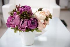 Фиолетовые пионы в белой вазе на белой таблице стоковые изображения
