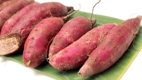 Фиолетовый сладкий картофель сырцовый на изоляте лист банана на белизне Стоковое Изображение RF