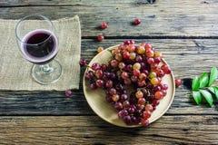 Фиолетовая плита виноградин, красный бокал, помещенный на старом деревянном столе Стоковые Фото