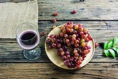 Фиолетовая плита виноградин, красный бокал, помещенный на старом деревянном столе Стоковые Изображения RF