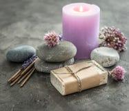 Фиолетовая свеча, бар домодельного мыла в бумаге стоковое фото
