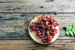 Фиолетовые виноградины на плите помещенной на старом деревянном столе Стоковое фото RF