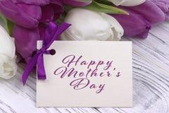 Фиолетовые и белые тюльпаны с белой бумагой на белых деревянных предпосылке и карточке помечая буквами счастливый день ` s матери Стоковые Изображения RF