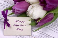 Фиолетовые и белые тюльпаны с белой бумагой на белых деревянных предпосылке и карточке помечая буквами счастливый день ` s матери Стоковые Изображения
