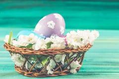 Фиолетовые и голубые пасхальные яйца в корзине с цветками деревянное предпосылки голубое пасха счастливая Стоковые Фотографии RF