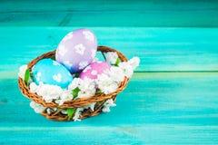 Фиолетовые и голубые пасхальные яйца в корзине с цветками деревянное предпосылки голубое пасха счастливая Стоковое фото RF