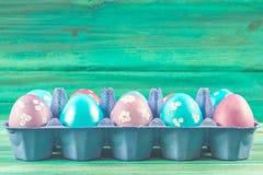 Фиолетовые и голубые пасхальные яйца в подносах картона деревянное предпосылки голубое пасха счастливая Стоковая Фотография RF