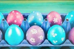 Фиолетовые и голубые пасхальные яйца в подносах картона деревянное предпосылки голубое пасха счастливая Стоковые Изображения RF