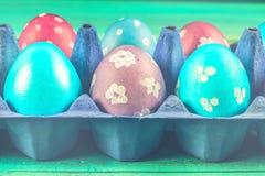Фиолетовые и голубые пасхальные яйца в подносах картона деревянное предпосылки голубое пасха счастливая Стоковые Фото