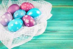 Фиолетовые и голубые пасхальные яйца на белой ткани деревянное предпосылки голубое пасха счастливая Стоковое фото RF